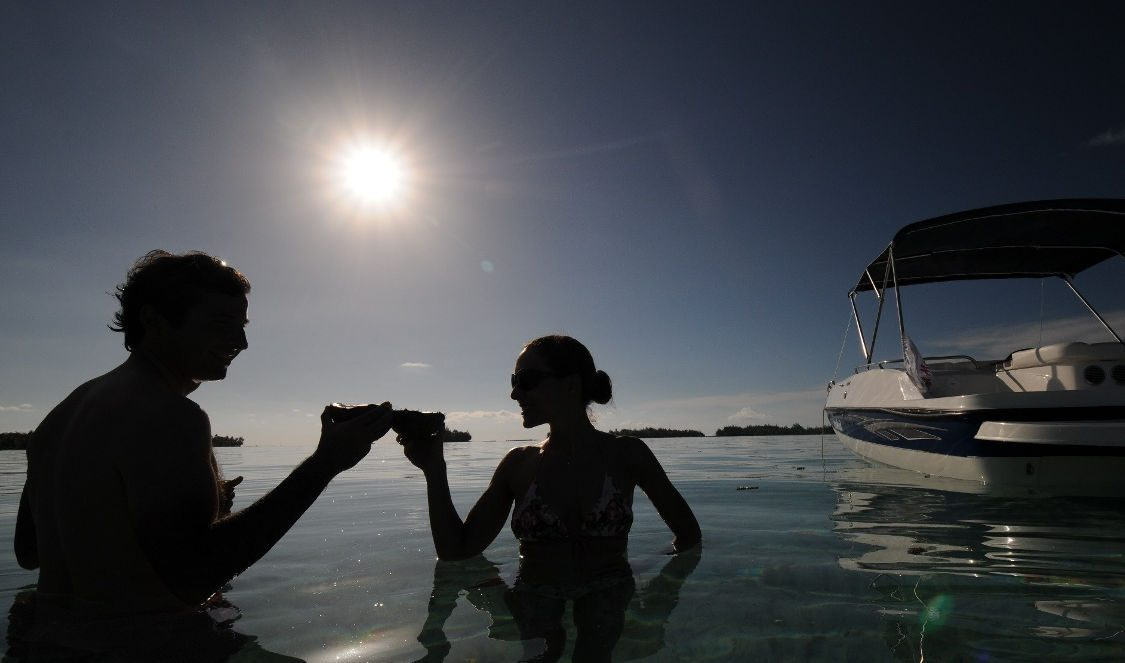 couple drinking champaign at sunset during private lover cruise in bora bora