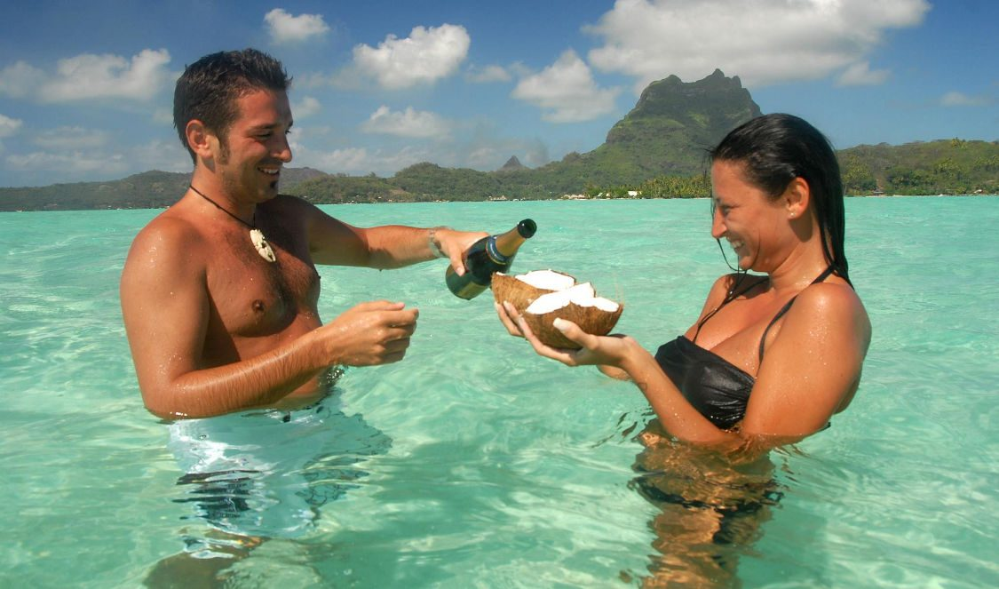 couple enjoying champaign in the lagoon at private lover cruise in bora bora for your vacation