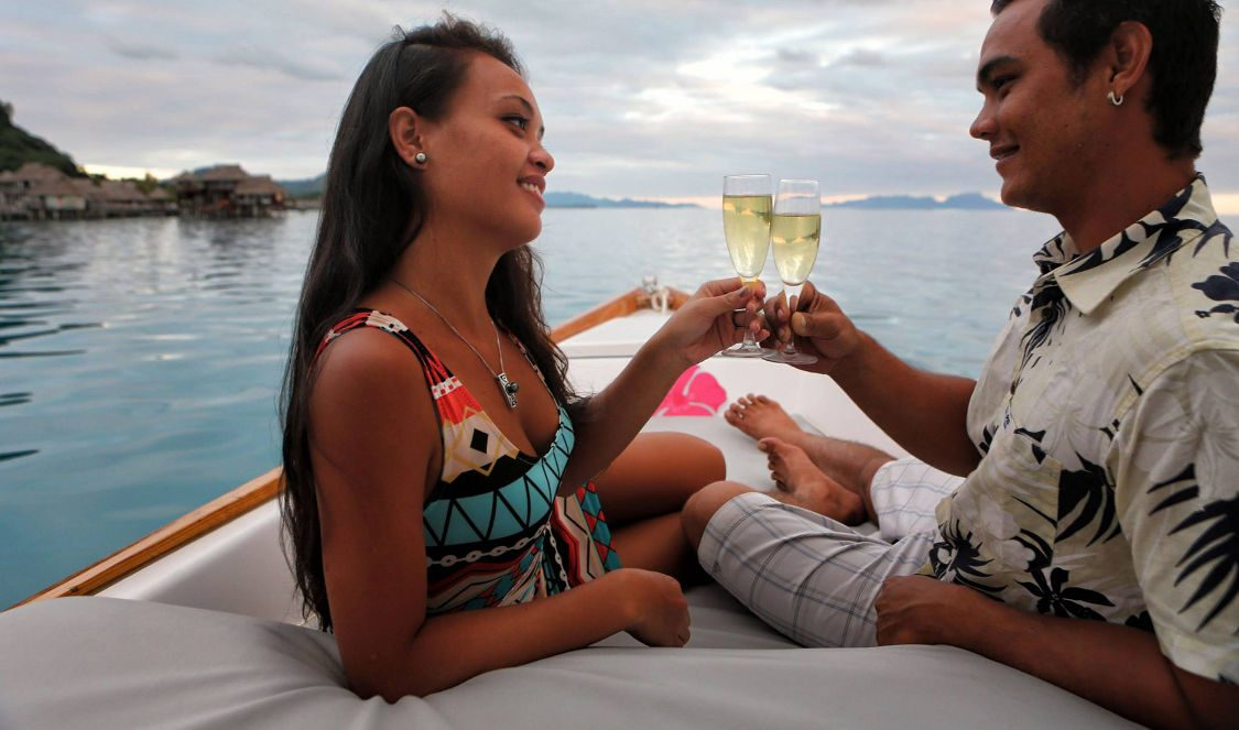 couple enjoying glass of champaign during sunset cruise in bora bora lagoon during holiday