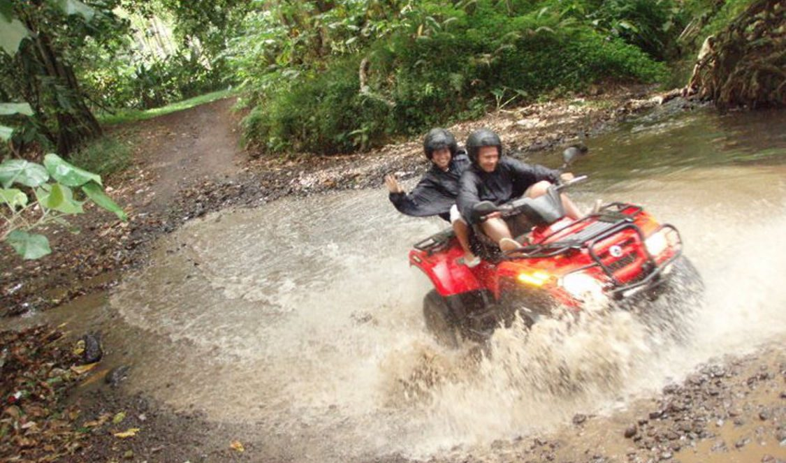 couple crossing river during atv quad tour in Moorea French Polynesia for your next holiday