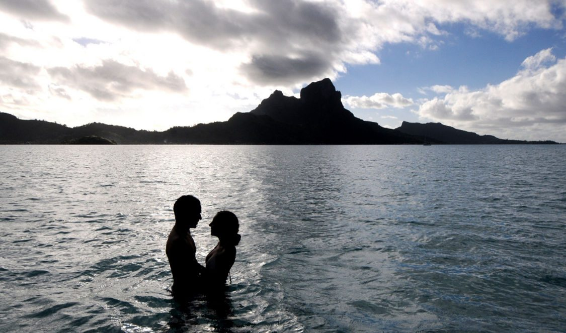 couple photoshoot enjoying private lover cruise in bora bora during their vacation