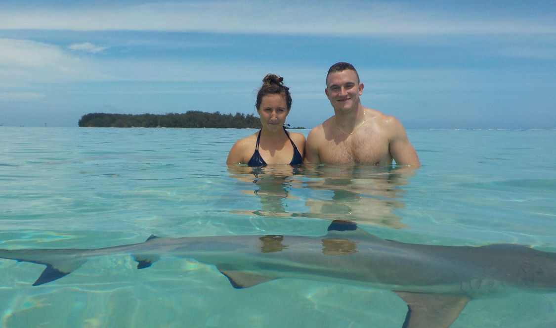 couple taking pics with small sharks during jetski tour in Moorea French Polynesia